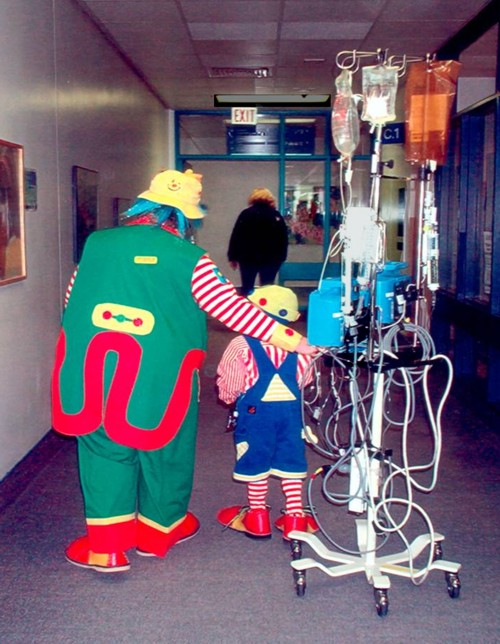 Clown Molly Penny walking in cooridor with hospitalized child dressed as a clown
